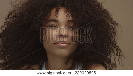 mixed race black woman portrait with big afro hair, curly hair in beige background smiling and laughing closeup