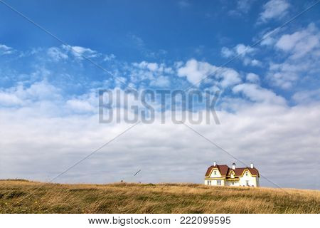 White wooden house, with red tile roof and yellow gables, on the horizon and isolated in a field of wild grass. Cap Aux Meules, Iles de la Madeleine, Canada.