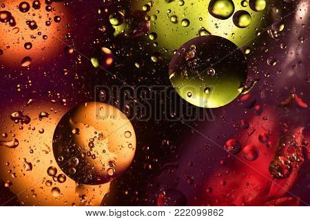 Colorful and bright background with circle oil drops that reflect yellow, orange, purple, green and red color. Color spots intentionally unfocused. Cosmic space concept.