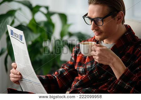 Tranquil guy holding the journal and cup in the hand. He is reading news with intent look and drinking coffee in bedroom