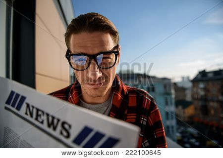 Portrait of satisfied guy standing on the balcony and holding the newspaper. He is looking at camera with intent look