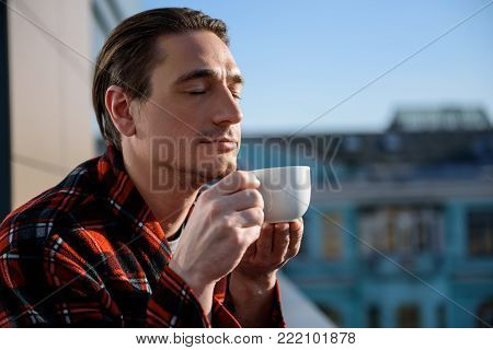 How it smells. Portrait of calm guy standing outside and holding a cup, he is smelling drink with closed eyes. Copy space in right side