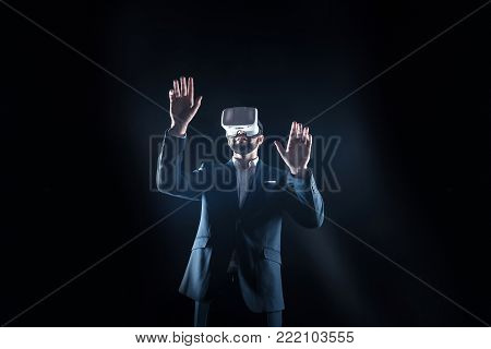 Virtual device. Handsome nice serious man wearing 3d glasses and pressing his hands to the virtual screen while being in 3d reality