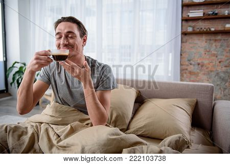 Waist up portrait of glad man holding a cup while sitting on bed. He is smiling and smelling tasty drink. Copy space in right side