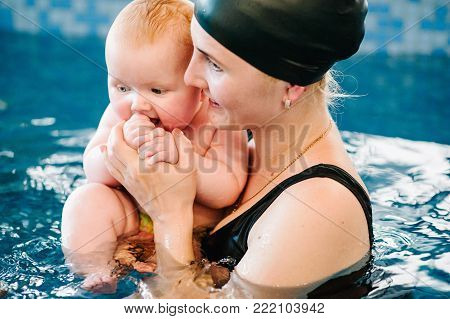 Young mother, happy little girl in the pool. Teaches infant child to swim. Enjoy the first day of swimming in water. Mom holds child preparing for diving. doing exercises. hand leading child on water