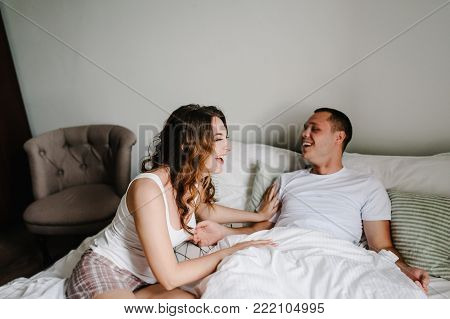 A man caresses a woman in bed. Love couple lying in a big bedroom. Love story. Emotions of happiness. Enjoying spending time together. I love you. Celebrating Saint Valentines Day.