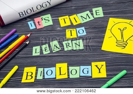 Education concept: Biology textbook, It's Time To Learn Biology inscription and colored pencils, black wooden background, top view