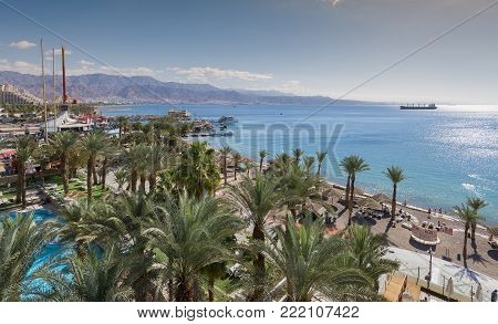 EILAT, ISRAEL - JANUARY 15, 2018: Aerial view on the Red Sea, central public beach and promenade in Eilat - famous vacation spot,  resort and recreational city in Israel and Middle East