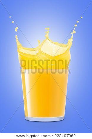 glass of splashing orange juice on blue background. Orange juice splash. Pouring orange juice