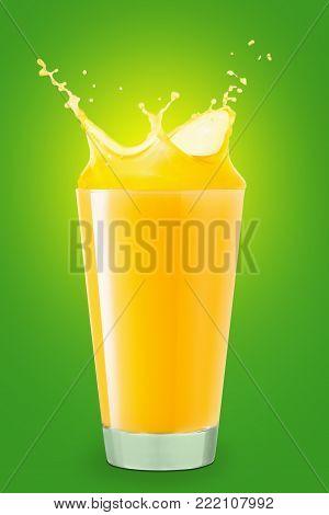 glass of splashing orange juice on green background. Orange juice splash. Pouring orange juice