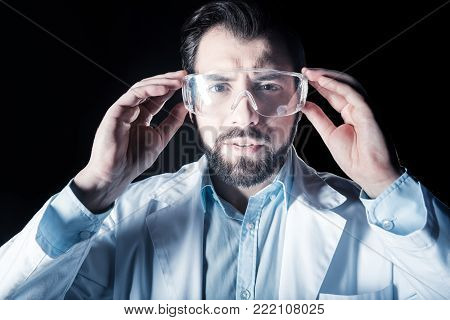 Real genius. Portrait of a smart nice bearded scientist wearing safety glasses while looking in front of him
