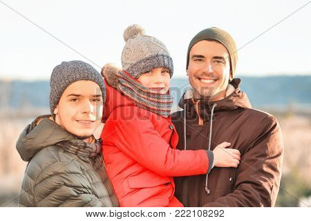 Male gay couple with adopted boy outdoors