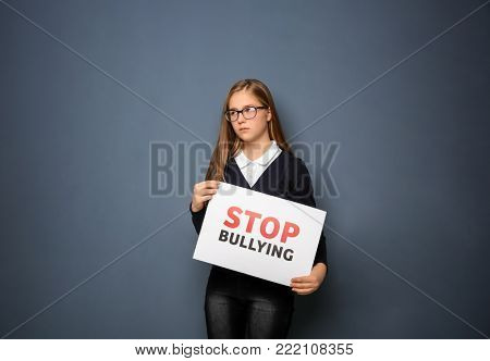 "Teenage girl holding sign ""Stop bullying"" on color background poster"