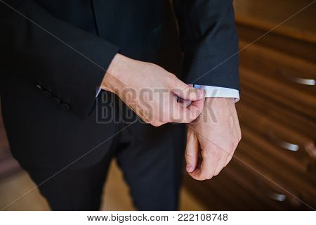Successful businessman in business suit with a tie on dark background. Stylish businessman. Confident businessman on the background of the gray wall. Young businessman. A focused businessman on the success. Successful businessman concept