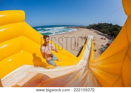 Beach Boy action thrill jump ride down high inflatable water slide summer holidays landscape.