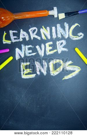 Education concept: Learning Never Ends inscribed with colored chalks on a black chalkboard, pencils and a beaker with orange liquid, top view