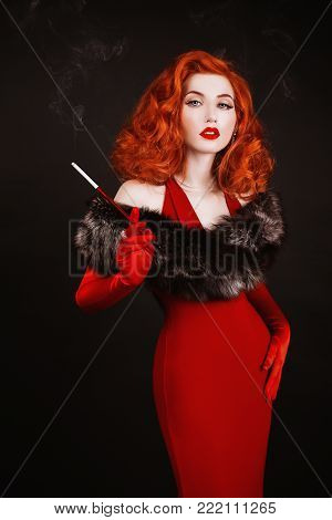Red-haired retro woman with curly hair in red retro dress and long retro gloves smoke. Retro girl is dressed in retro style with fur and the mouthpiece with a cigarette. A retro woman with pale skin and red hair