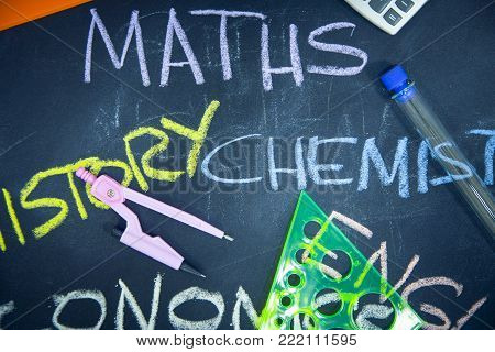 Education concept: Names of school subjects inscribed on a black chalkboard with colored chalks and stationary, close up, top view