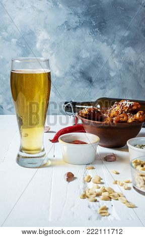 Buffalo style chicken wings served with cold beer on white wood background