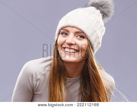 Attractive woman in winter wool cap and gray sports thermolinen underwear for skiing training studio shot on violet.