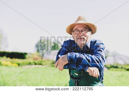 Portrait of a senior gardener standing in a garden with a shovel. Gardener's jpb.