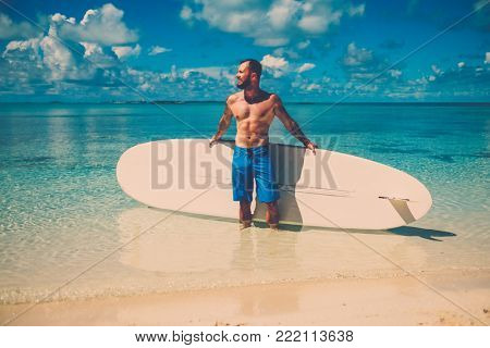 Man with Stand Up Paddle Board on the beach in Bahamas