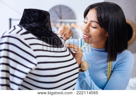 Nice stitches. Cheerful young pleased tailor feeling satisfied while looking at the well done stitches on a new beautiful striped blouse