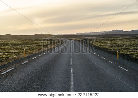 Textured roadway with orange roadside pillars between the green fields on the background of the mountains and cloudy sunset sky in Iceland. Horizontal.