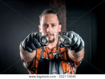 Tattoo artist poses for the camera in tattoo parlour.