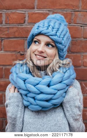 Young blonde woman in blue knitted hat, blue khitted infinity scarf and grey sweater make posing with brick wall on the background