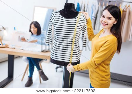 Skilled tailor. Positive emotional skilled worker of an atelier holding a tape measure and smiling cheerfully while standing next to the mannequin with a lovely striped blouse on it