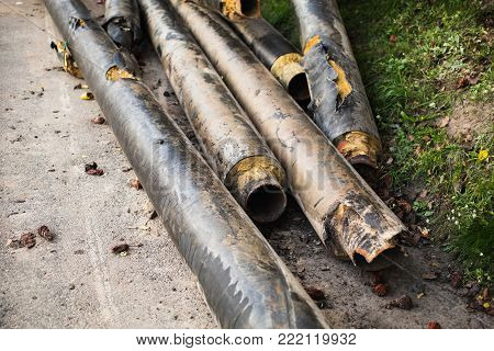 Water pipes with insulation lie on the grass. Pipe for water. New water pipe. Pipe for heating. Pipe with drops of water. Pipe with thermal insulation