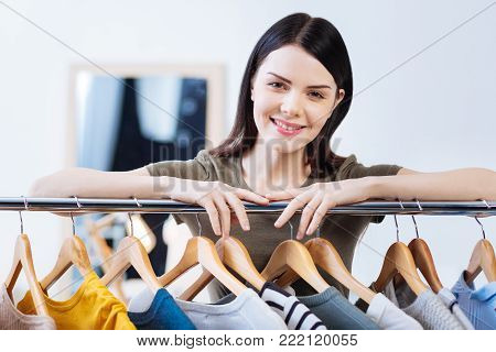Peaceful smile. Polite young pretty woman standing in a fashionable atelier and smiling while her hands touching a convenient clothes rail