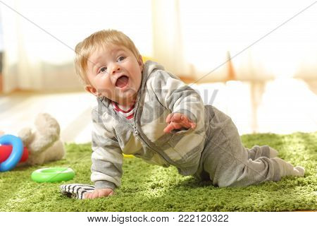 Happy baby crawling and laughing on a green carpet at home
