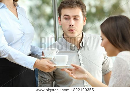 Disloyal boyfriend looking at breast of a waiter in front of his distracted girlfriend