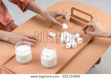 Pile of marshmallows and two glasses with milk on the orange metal tray on the same table in the studio. Couple of girls sitting near the table. One woman holds the  marshmallow in her hand. Closeup.