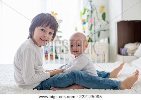 Little Toddler Boy, Playing With His Little Brother At Home