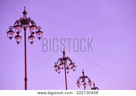 wrought streetlamps on the background of ultraviolet or magenta sky