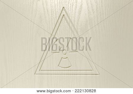 Sign of radioactive contamination on light wooden surface. Warning of danger.