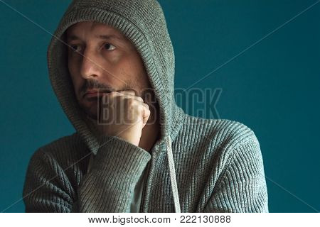 Portrait of thoughtful pensive man thinking with hand on chin