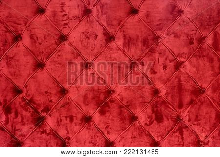 Closeup of elegent luxury red velvet sofa pattern with buttons