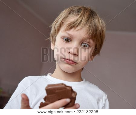 Funny little blond boy after eating bar of chocolate