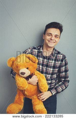 Man holds teddy bear on a light blue background, copy space. Pretty toy concept. Man hugs cute toy bear tight. Guy with happy face plays with red soft toy. Vintage filter.