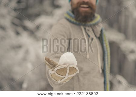 Hand with snowball in mitten of blurred bearded hipster in thermal jacket, scarf in snowy forest. Temperature, freezing, cold snap, snowfall, snow. poster