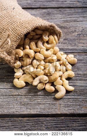 Cashew nuts in burlap bag on wooden background . Healthy food