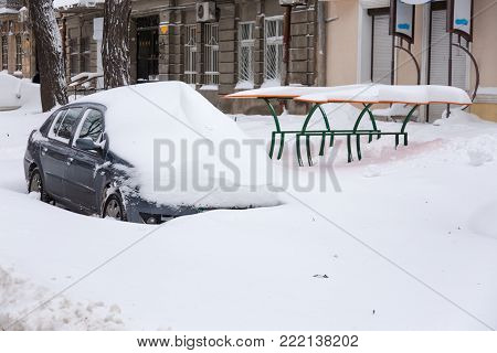Snow drifts in the city on a winter frosty day. Car blocked in the yard by snowdrifts after the heavy snow storm