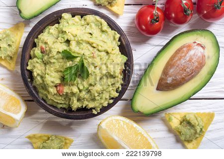 Guacamole with ingredients : avocado , lemon and tomatoes . Mexican food