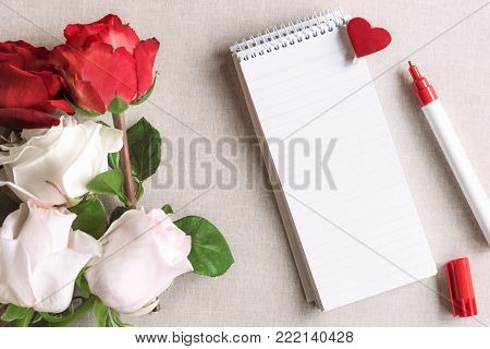 Roses and a blank spiral notebook with heart - Open spiral notebook with stripes and a wooden clip with red heart pinned on it and a bouquet of white and red roses, on a vintage fabric background.