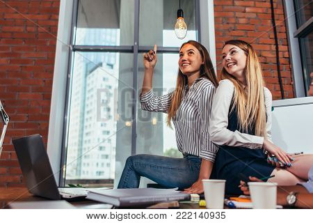 Students sitting together on desk in classroom, a girl pointing at light bulb like having a brilliant idea