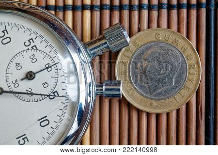 Turkish coin with a denomination of one lira and stopwatch on wooden table - back side